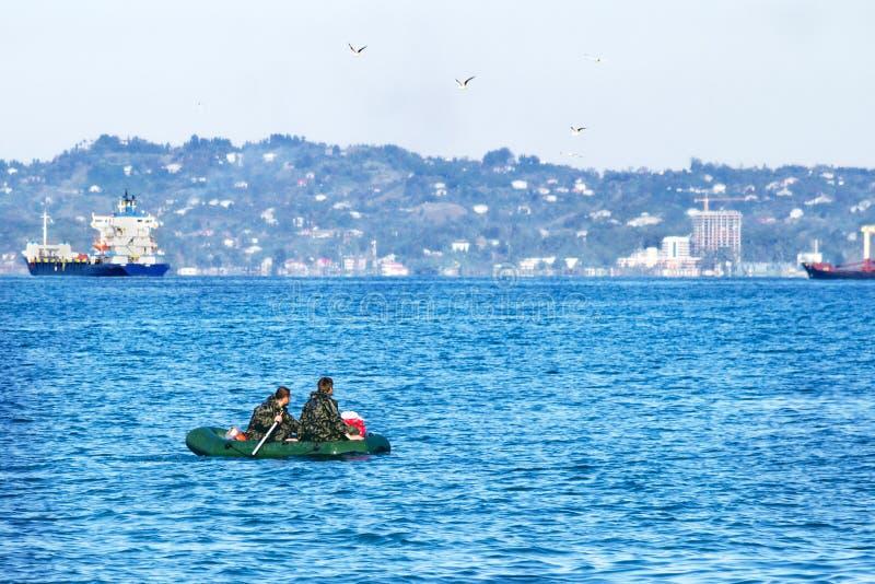 El barco inflable de goma con los hombres en camuflaje uniforma en el mar imagenes de archivo