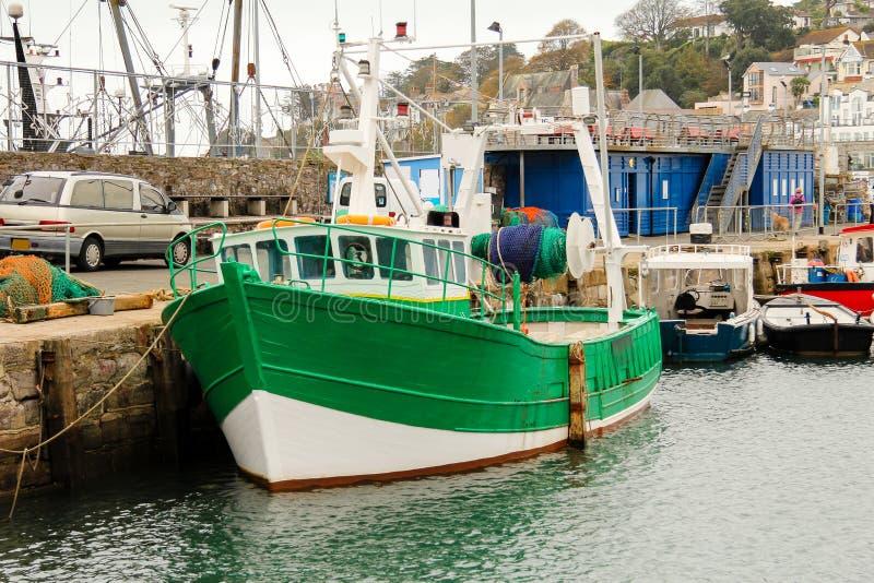 El barco rastreador pesquero verde amarró longside la pared del puerto, Brixham, Devon del sur fotos de archivo