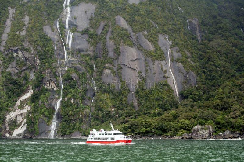 El barco turístico cruza en el fiordo de Milford Sound, isla del sur de Nueva Zelanda fotografía de archivo