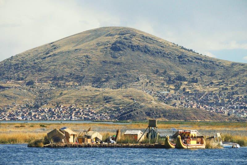 El barco y las casas de lámina tradicionales en el lago Titicaca, un lago grande, profundo en los Andes en la frontera de Bolivia foto de archivo libre de regalías