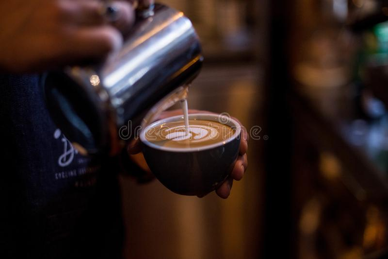 El barista profesional dibuja arte del latte en la taza de café foto de archivo libre de regalías