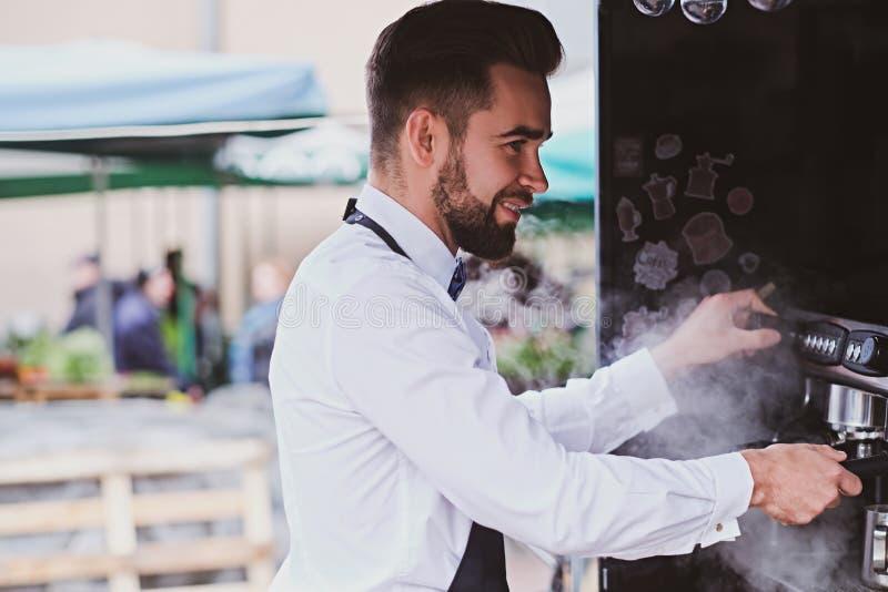 El barista sonriente en la camisa blanca est? preparando el caf? usando el vapor foto de archivo