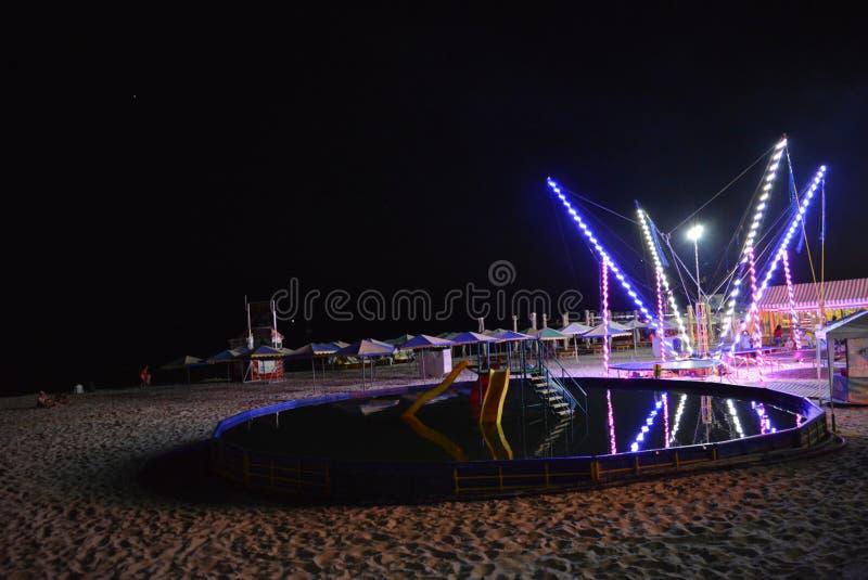 El basar de la noche en la playa del Mar Negro con una piscina del ` s de los niños, un trampolín se vistió con las bandas del di fotos de archivo