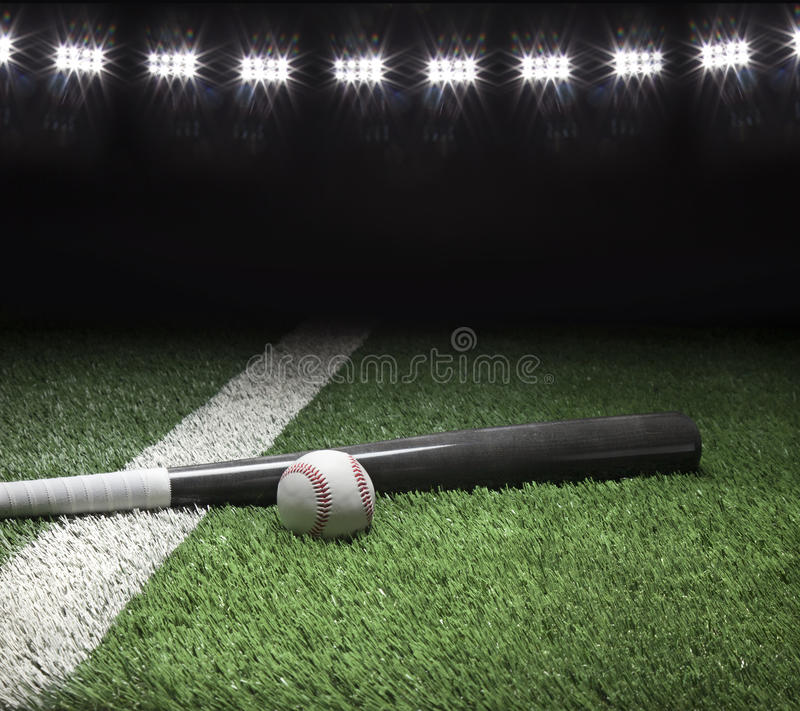 El bate de béisbol y la bola grises en campo con el estadio se enciende foto de archivo libre de regalías