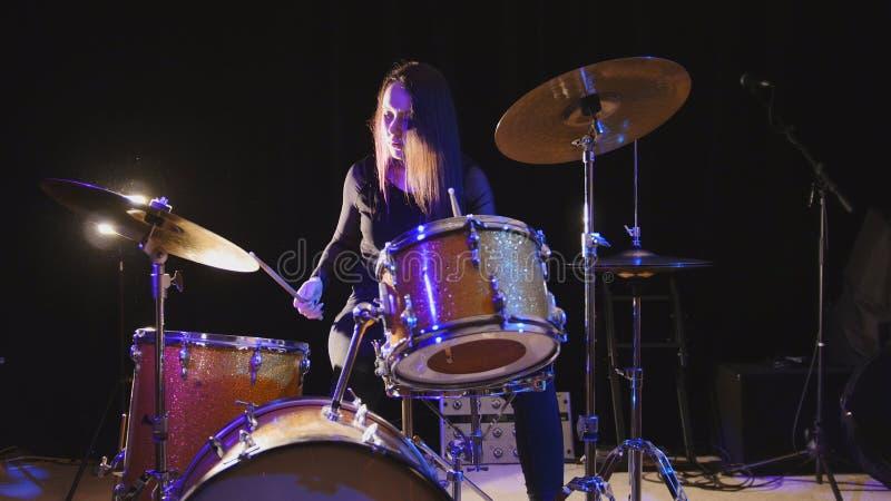 El batería emocional de la muchacha, modelo atractivo del pelo del youngblack juega los tambores fotografía de archivo libre de regalías