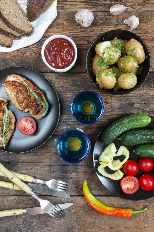 El Bbq, verduras, asó a la parrilla el chicke, comensal americano, filete de la carne asada, vino rojo, tabla de madera, visión s imagen de archivo
