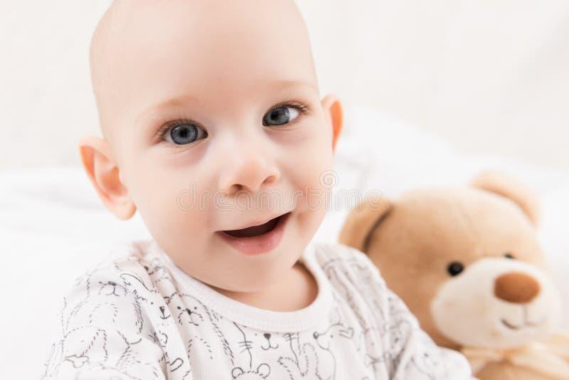 El bebé adorable que se sienta en una cama, jugando con el juguete refiere una cama Niño recién nacido que se relaja imagenes de archivo