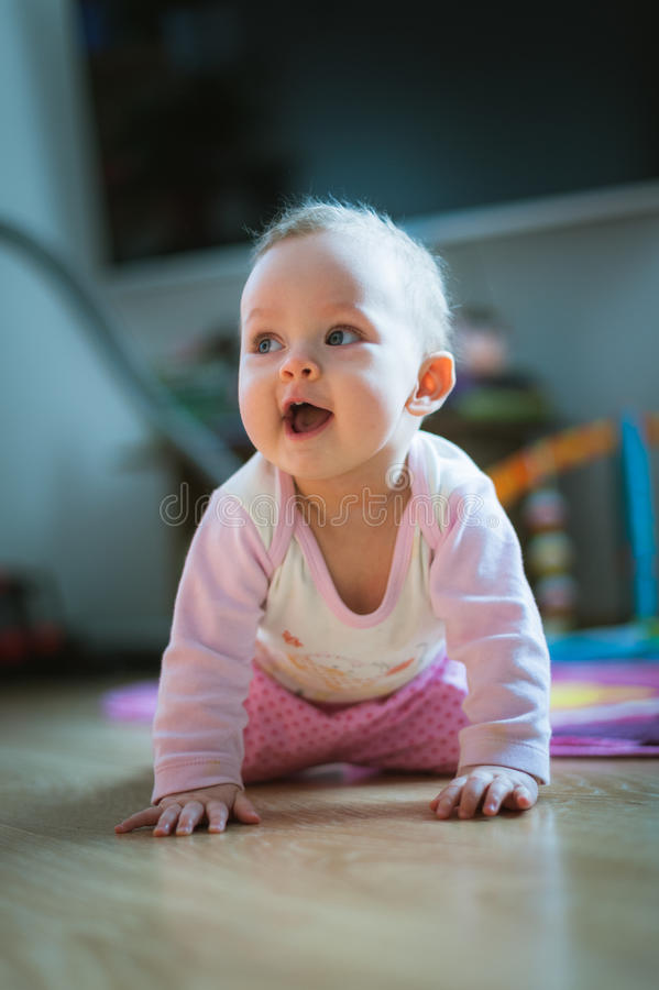 El bebé adorable se arrastra en todo el piso de los fours en fotos de archivo libres de regalías