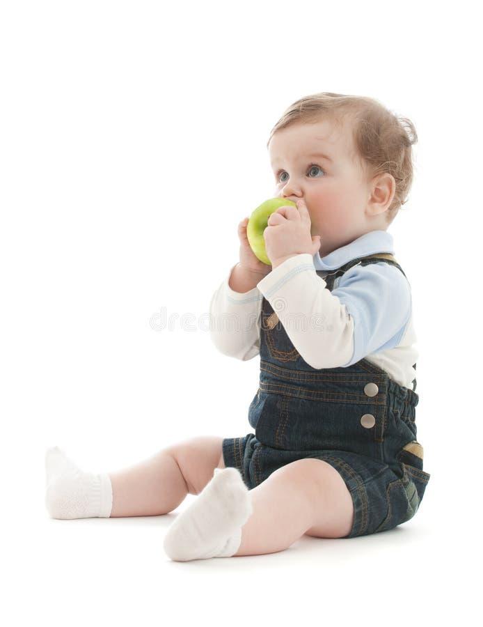 El bebé adorable sienta y come la manzana verde foto de archivo libre de regalías