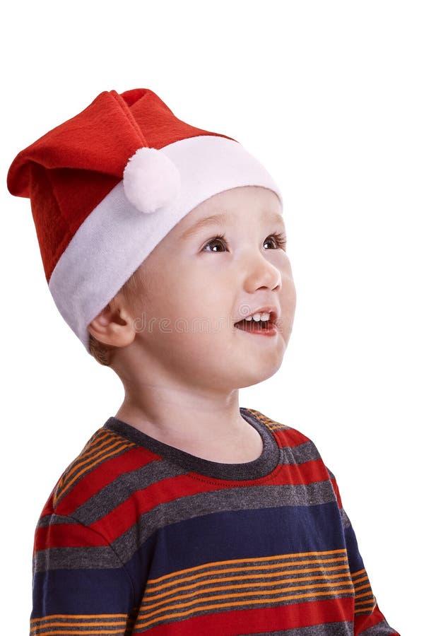 El bebé aislado en blanco, con un casquillo de Papá Noel, mirando sorprendió a imagen de archivo