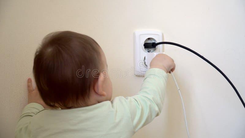 El beb? alcanz? el z?calo electical y unplushed el cable del cargador, hazaard del usb unsefety en casa con los peque?os ni?os foto de archivo libre de regalías