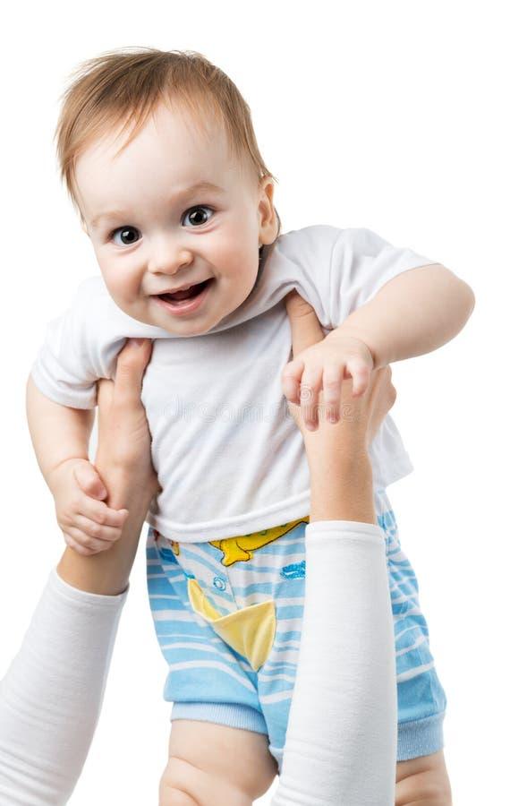 El bebé alegre lanza para arriba en las manos fotografía de archivo