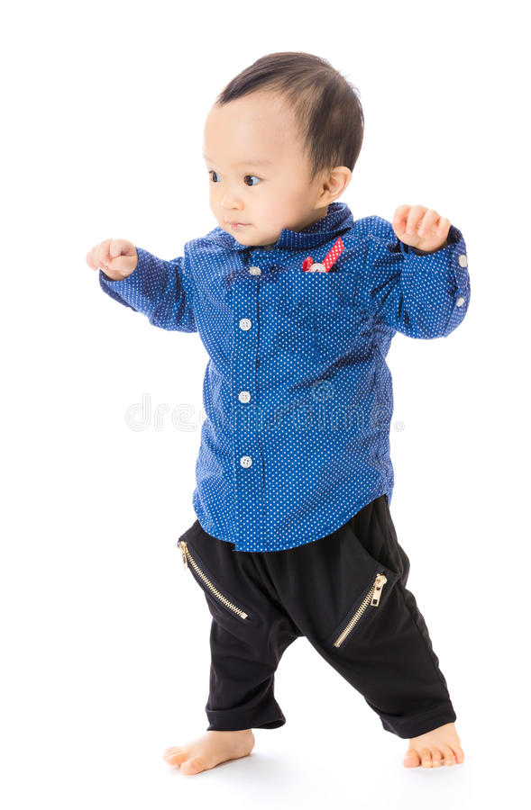 El bebé asiático aprende caminar foto de archivo