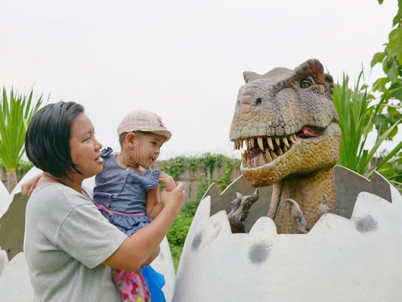 El bebé asiático, así como su tía, goza el mirar y el tocar de un dinosaurio fotografía de archivo