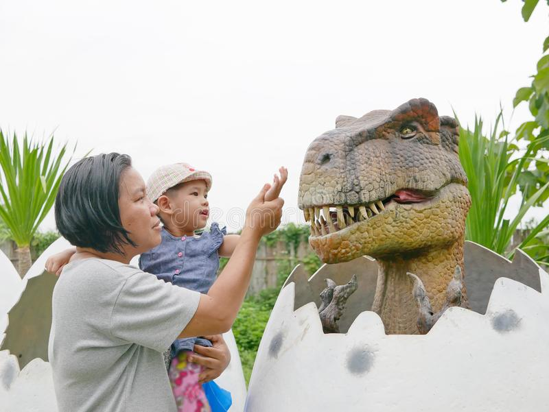 El bebé asiático, así como su tía, goza el mirar y el tocar de un dinosaurio imagen de archivo