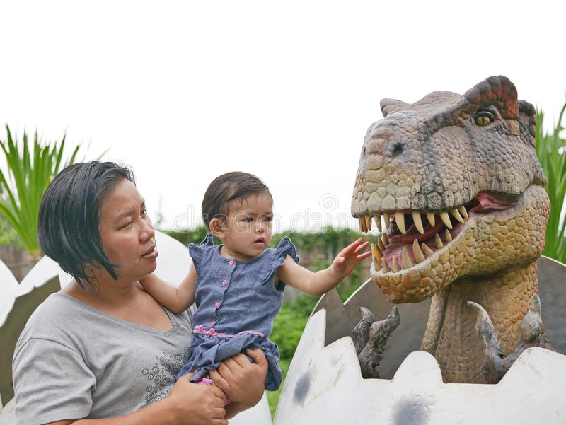 El bebé asiático, así como su tía, goza el mirar y el tocar de un dinosaurio fotografía de archivo libre de regalías
