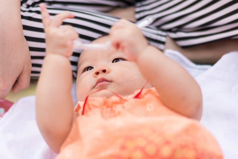 El bebé asiático goza el jugar del juguete en el parque fotos de archivo