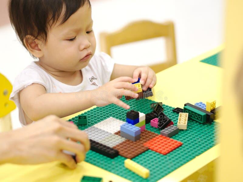 El bebé asiático que juega rompecabezas juega con el padre en la tabla amarilla interior imagen de archivo libre de regalías