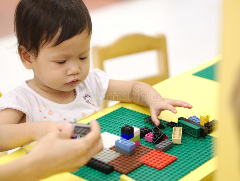 El bebé asiático que juega rompecabezas juega con el padre en la tabla amarilla interior imágenes de archivo libres de regalías