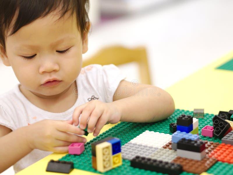 El bebé asiático que juega rompecabezas juega con el padre en la tabla amarilla interior imagen de archivo