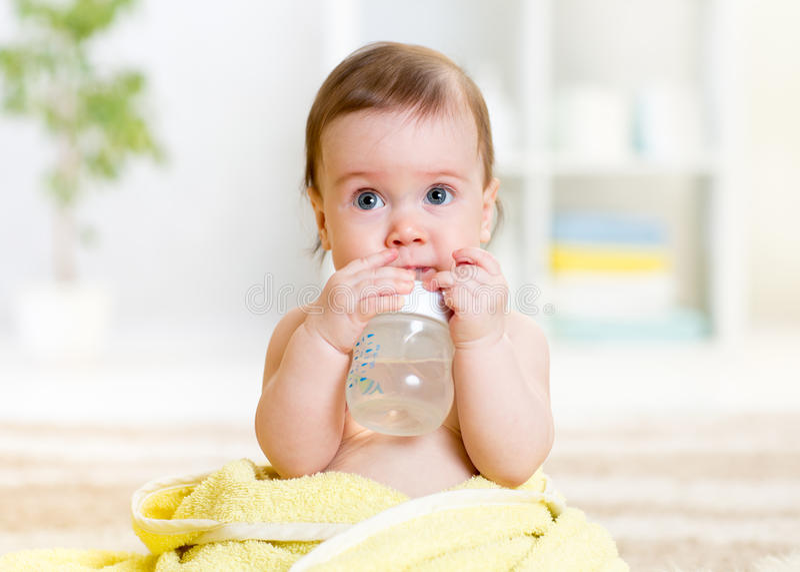 El bebé bebe el agua de la botella que se sienta con la toalla foto de archivo