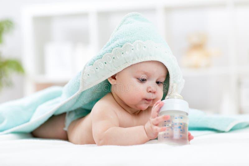 El bebé bebe el agua de la toalla cubierta botella después de baño fotografía de archivo