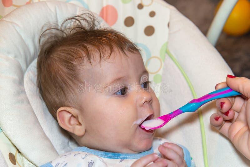 El bebé come la comida sólida por primera vez imagen de archivo libre de regalías