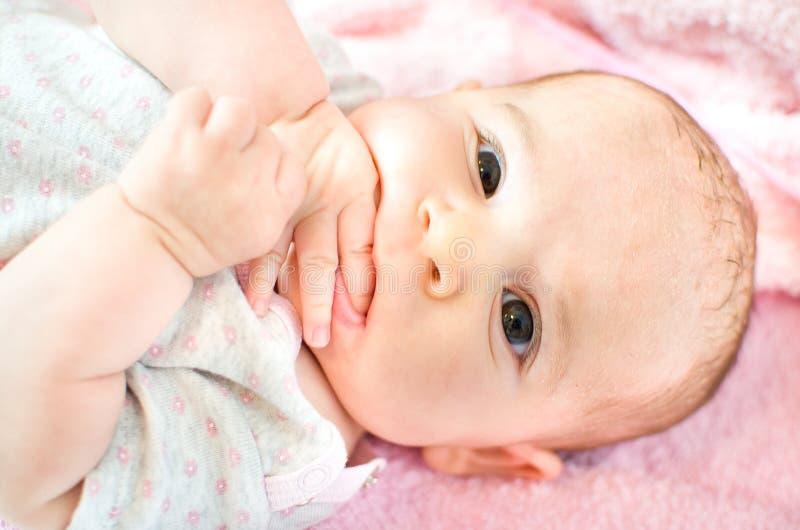 El bebé come las manos foto de archivo