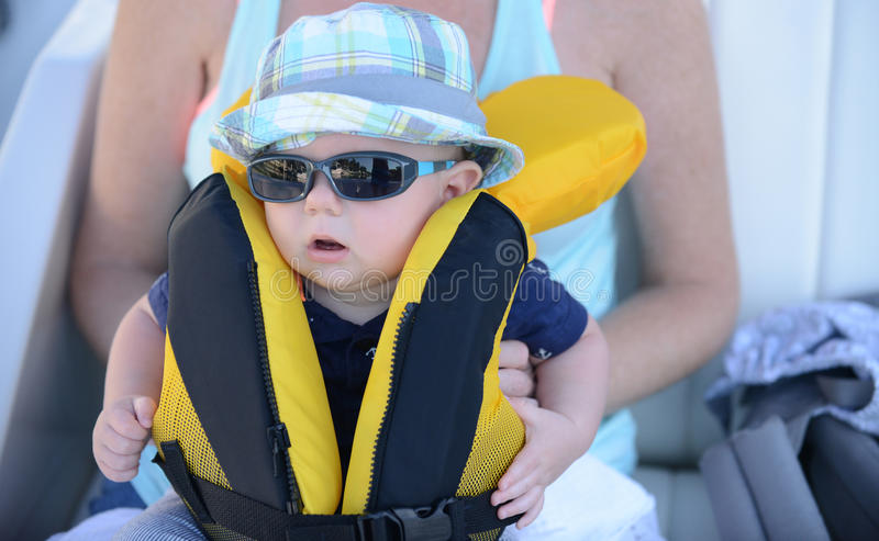 El bebé con el chaleco salvavidas en eso necesita ser relampagado para arriba con los sunglass foto de archivo libre de regalías