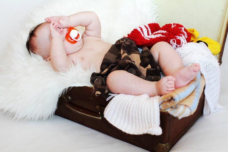 El bebé con el maniquí miente en una maleta con ropa fotografía de archivo libre de regalías