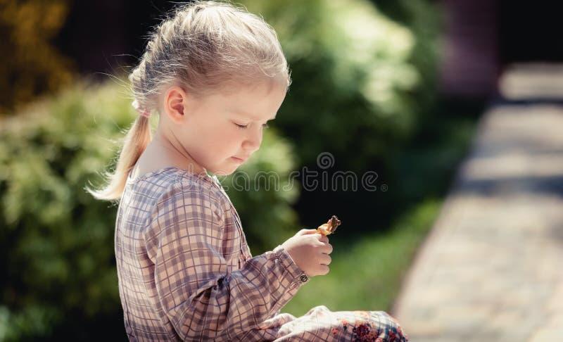 El bebé con el pelo largo y el vestido hermoso se sienta en el doorste fotos de archivo