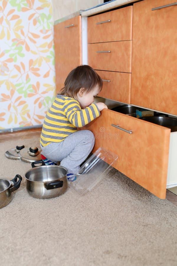 El bebé curioso mira en cajón en cocina imagen de archivo