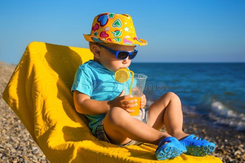 El bebé del muchacho en vidrios y sombrero de sol en la playa bebe el jugo fotografía de archivo libre de regalías