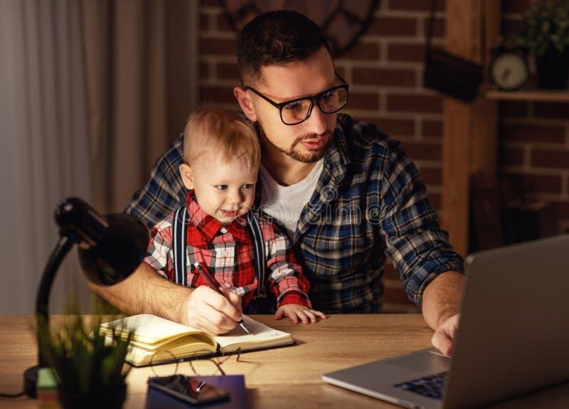 El bebé del padre y del hijo trabaja en casa en el ordenador en oscuridad fotografía de archivo