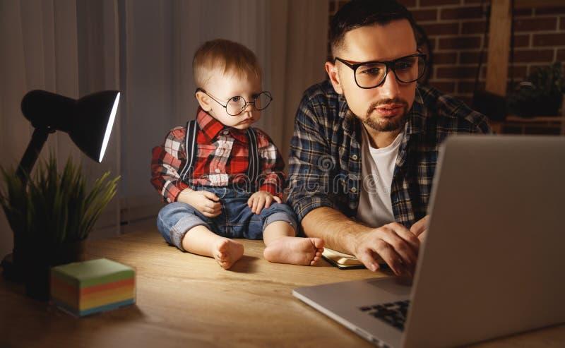 El bebé del padre y del hijo trabaja en casa en el ordenador en oscuridad imagen de archivo