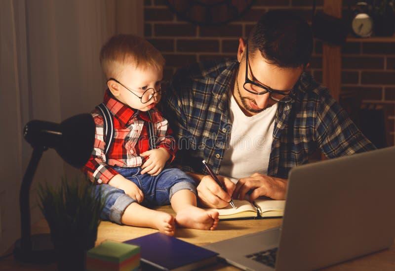 El bebé del padre y del hijo trabaja en casa en el ordenador en oscuridad fotos de archivo