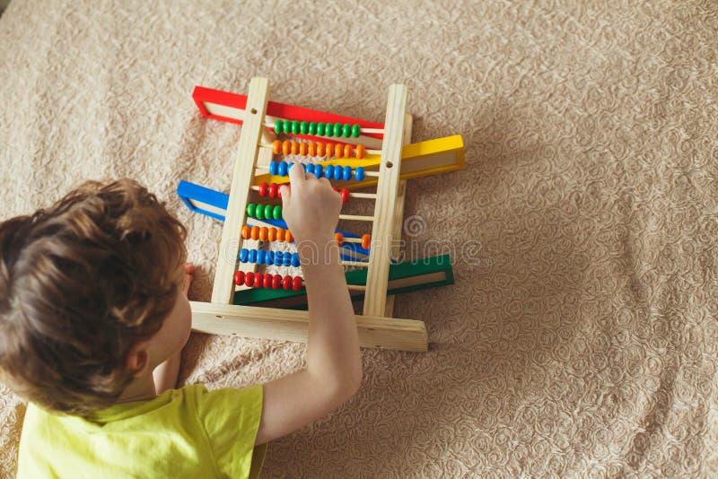 El bebé del preescolar aprende contar Niño lindo que juega con el juguete del ábaco Niño pequeño que tiene la diversión dentro en fotos de archivo