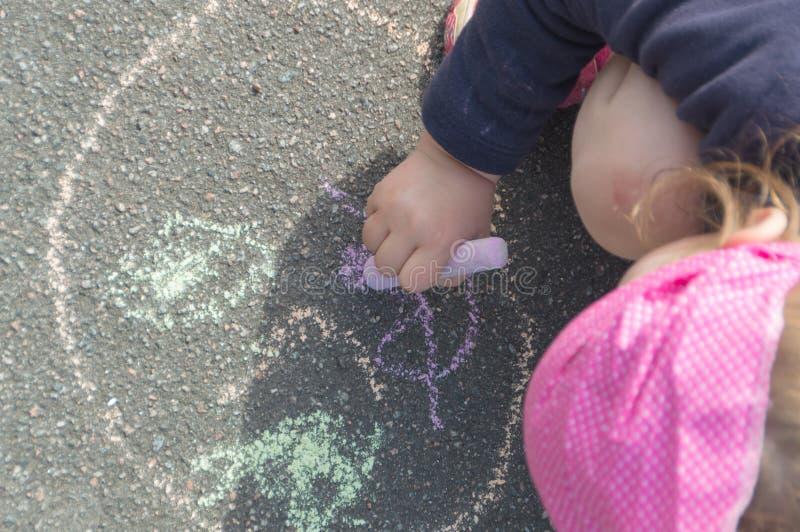 El bebé dibuja en el pavimento, cierre para arriba foto de archivo libre de regalías
