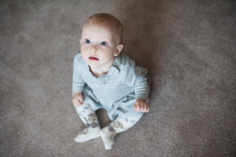 El bebé divertido lindo laughting y mira para arriba la cámara Ciérrese encima del retrato de la niña en vestido gris fotografía de archivo