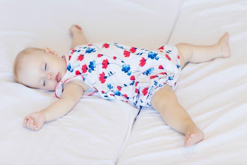 El bebé duerme en una hoja blanca recién nacida, niña se cayó dormido en la cama imagenes de archivo