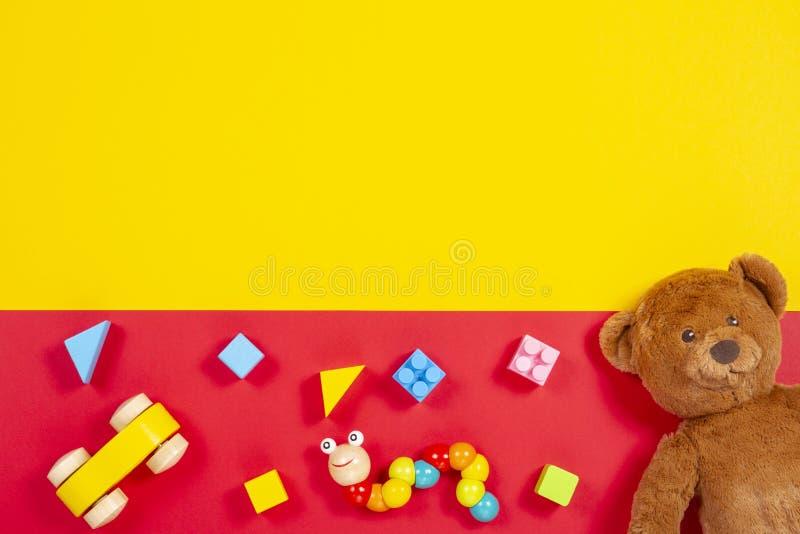 El bebé embroma el fondo de los juguetes Oso de peluche, coche de madera, ladrillos coloridos en fondo rojo y amarillo foto de archivo