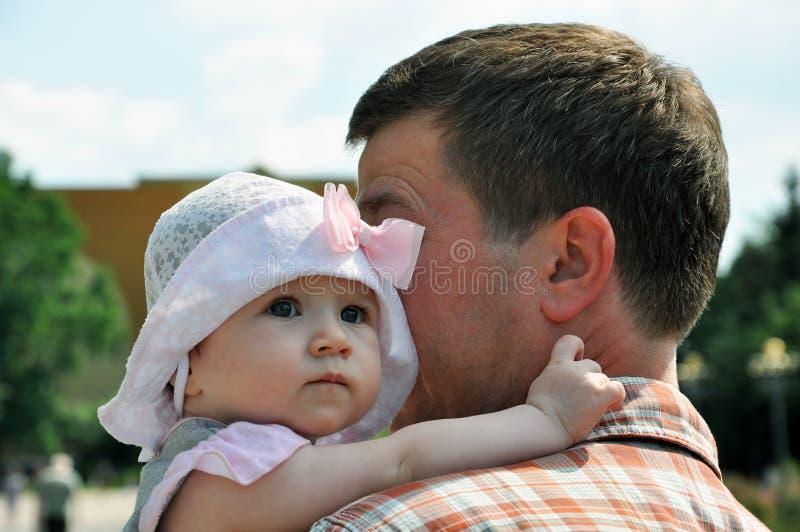 El bebé en sombrero ligero abraza a su padre fotografía de archivo libre de regalías