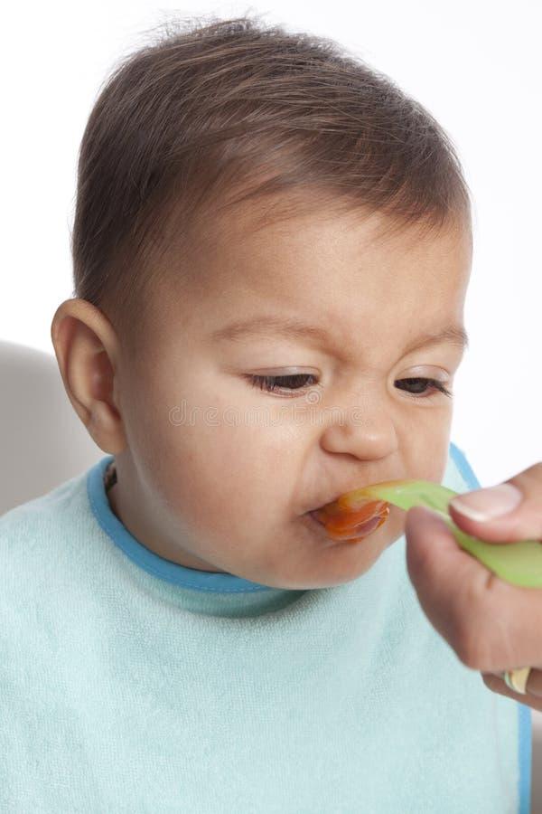 El bebé es aversiones que come zanahorias fotografía de archivo