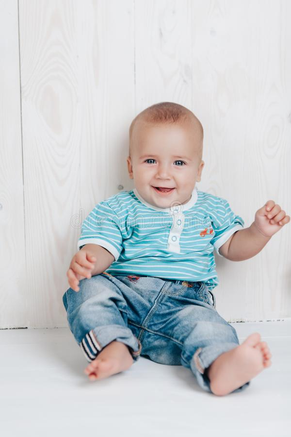 El bebé es el sentarse sonriente muy lindo en el piso contra un fondo ligero fotografía de archivo