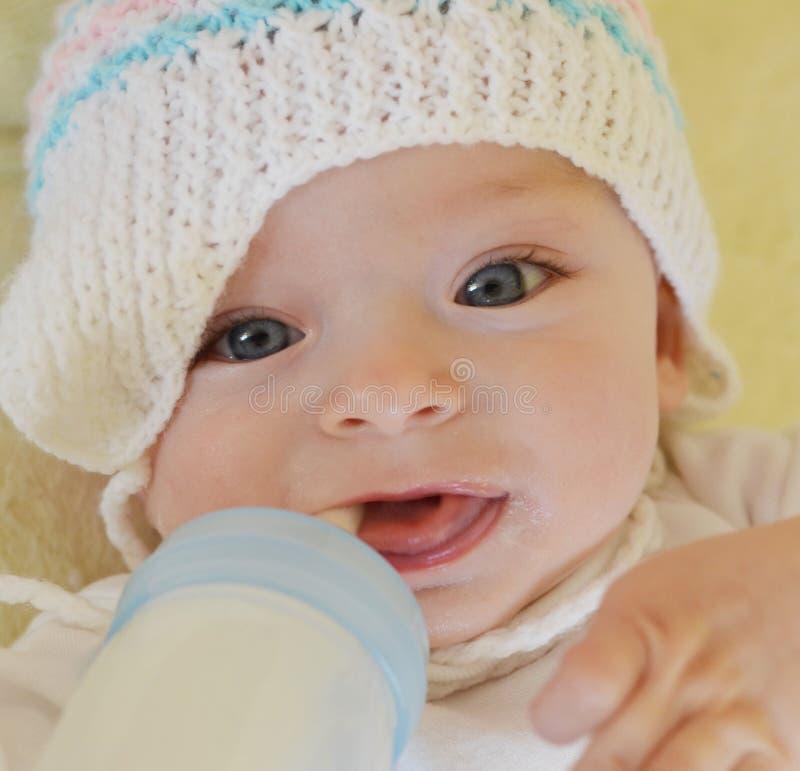 El bebé es sonriente y que juega con una botella fotos de archivo libres de regalías