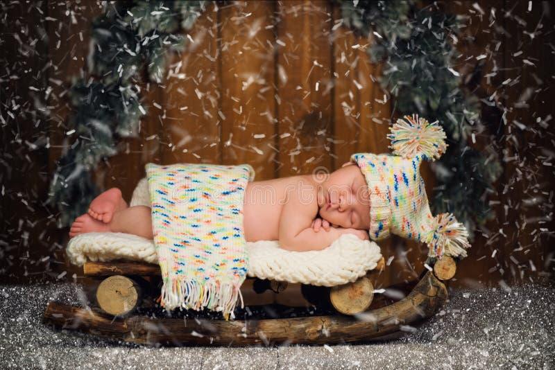 El bebé está durmiendo en trineos de madera ` S Eve del Año Nuevo imágenes de archivo libres de regalías