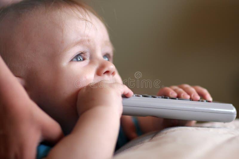 El bebé está mordiendo el telecontrol fotografía de archivo