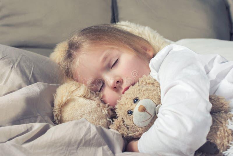 El bebé está rápidamente dormido abrazando un oso de peluche Niña con el pelo rubio en cama imagen de archivo libre de regalías
