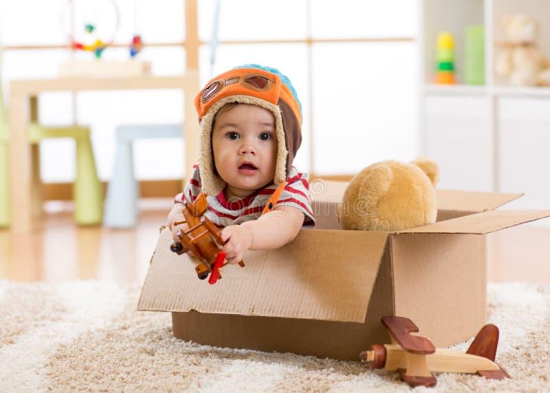 El bebé experimental del aviador con el juguete del oso de peluche juega en caja de cartón foto de archivo libre de regalías