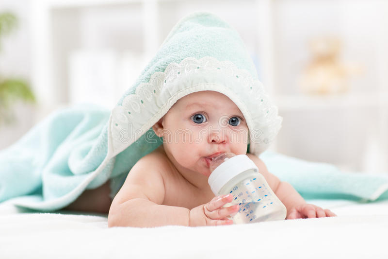 El bebé feliz bebe el agua de la toalla envuelta botella después de baño imágenes de archivo libres de regalías